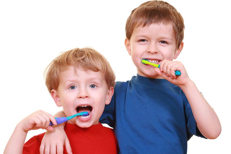 two boys brushing their teeth