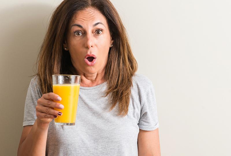 Surprised woman drinking orange juice